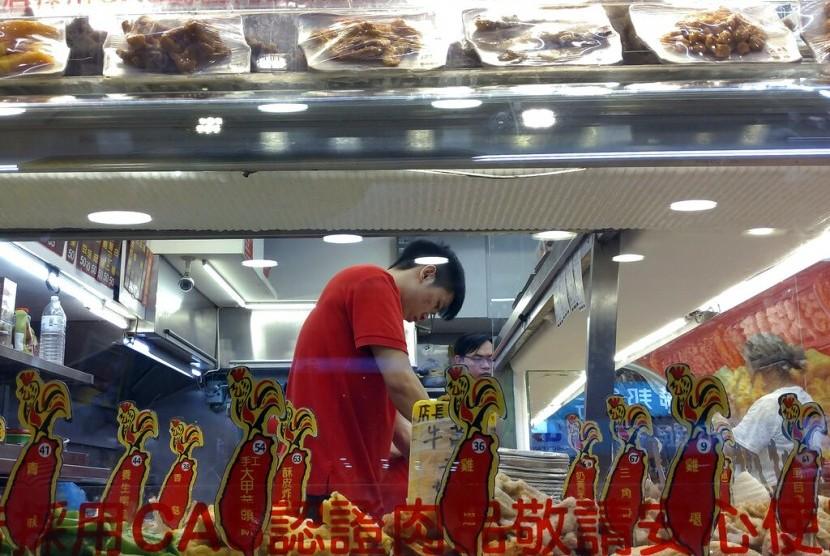 Pegawai menyiapkan makanan di pasar malam Taipei, Taiwan, belum lama ini.