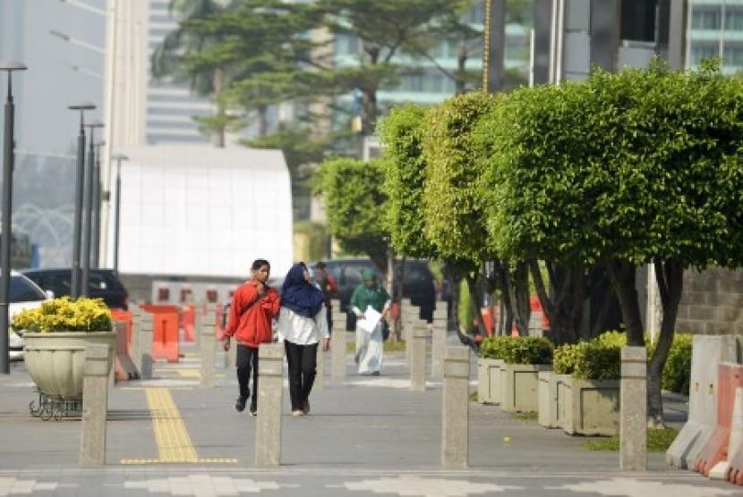 Pejalan kaki berjalan di trotoar MH Thamrin, Jakarta.