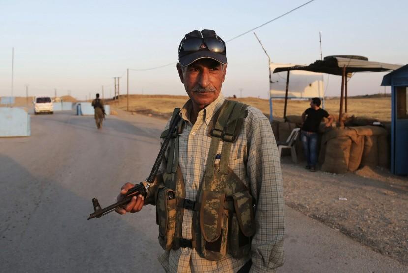 Pejuang Kurdi saat menjaga kamp pengungsi di Derike, Suriah, Ahad (10/8)