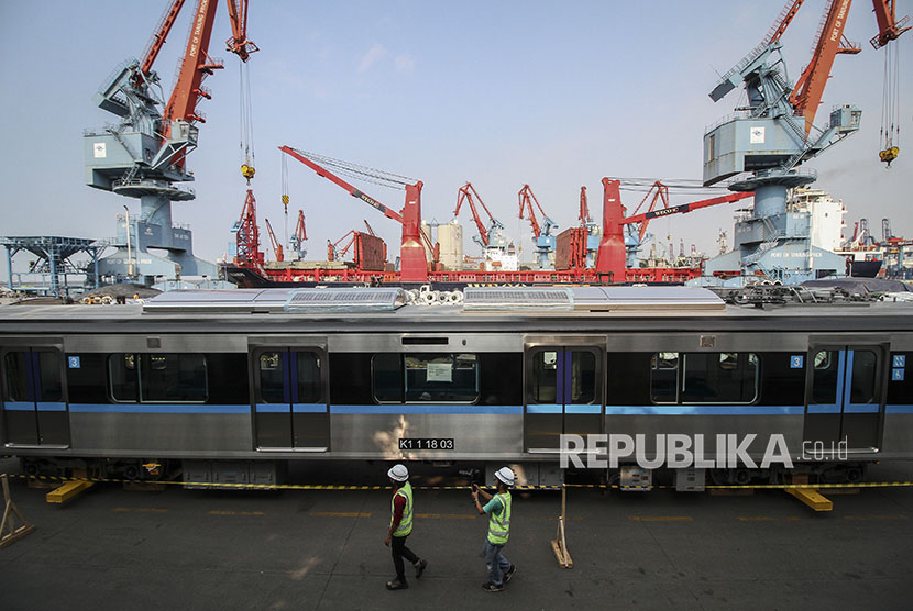 Pekerja berjalan di samping gerbong kereta MRT di Tempat Penimbunan Sementara (TPS) dermaga 101, Pelabuhan Tanjung Priok, Jakarta, Kamis (5/4).