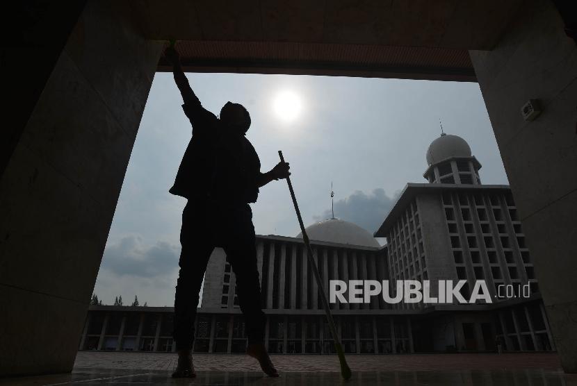 Pekerja Go-clean yang merupakan sub instansi dari Go-jek membersihkan tiang penyangga Masjid Istiqlal yang berada di Jakarta Pusat, Kamis (15/6).
