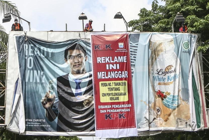 Pekerja melepaskan reklame yang melanggar izin di jalan POM IX Palembang, Sumatera Selatan, Kamis (6/12/18).