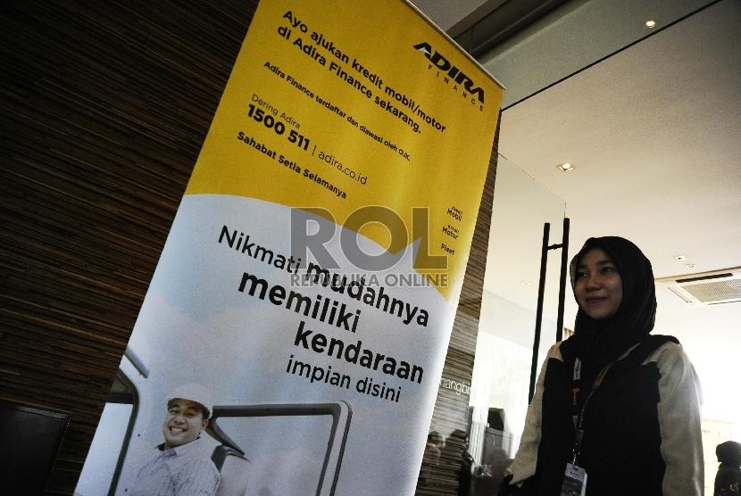 Pekerja melintas berlatar belakang penyaluran kredit Adira Finance di Jakarta (ilustrasi)