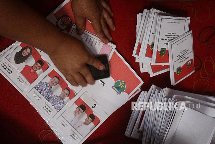 Pekerja melipat dan menyortir surat suara Pilkada Malang yang diikuti tiga pasangan calon di Kantor KPU Malang, Jawa Timur, Selasa (29/5).