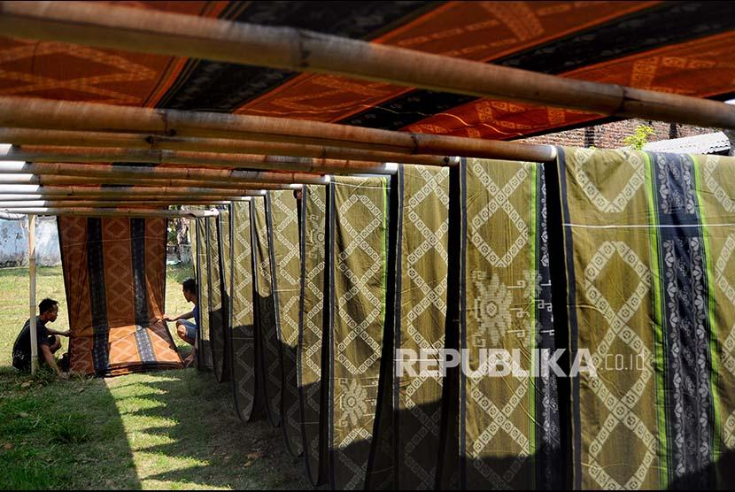 Pekerja melipat kain tenun yang dibuat menggunakan teknik Alat Tenun Bukan Mesin (ATBM) di Pekalongan, Jawa Tengah, Kamis (1/6). Kain tenun yang dibuat untuk bahan sarung tersebut dijual Rp9000-Rp70.000 per meter dan dipasarkan hingga ke Pulau Sumatra.