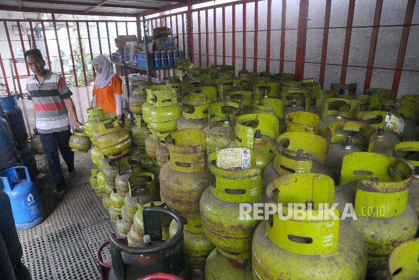 Pekerja mellayani pembeli gas elpiji tiga kilo di tempat penjualan gas di Jakarta, Ahad (2/4).