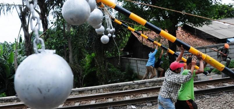 Pekerja memasang bola-bola besi penghalang penumpang atap gerbong kereta api di jalur kereta api Tambun-Bekasi, Bekasi, Jawa Barat, Selasa (17/1). (Republika/Aditya Pradana Putra)