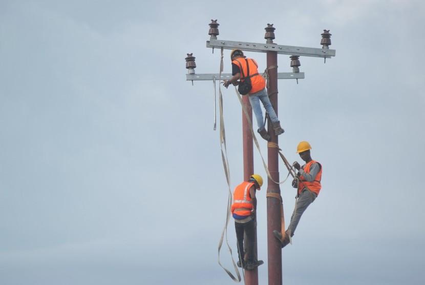 Pekerja memasang jaringan di tiang listrik baru di kawasan Air Tawar, Padang, Sumatera Barat, Selasa (8/1). Kementerian Energi dan Sumber Daya Mineral memutuskan tidak menaikkan tarif dasar listrik (TDL) bagi konsumen listrik subsidi dan non-subsidi pada triwulan I 2019.