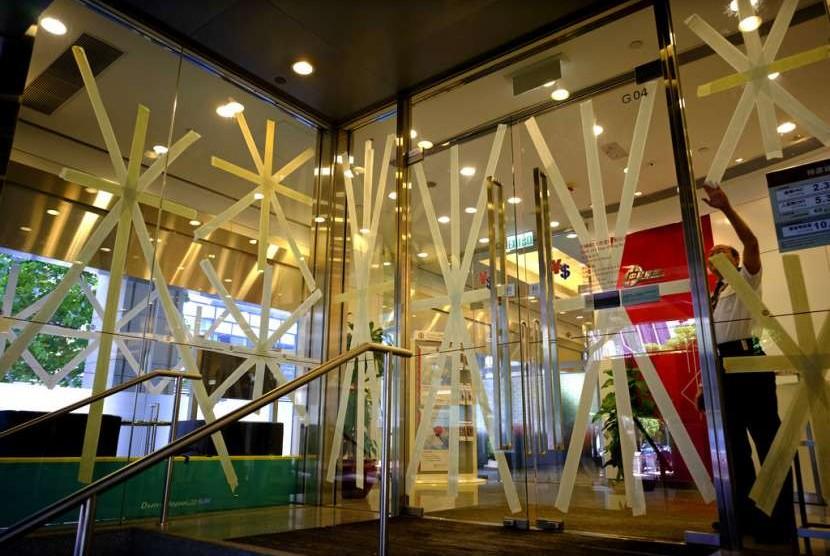 Pekerja memasang selotip di kaca banguanan di HK sebagai antisipasi amukan topan Mangkhut. Topan Mangkhut sudah menghantam Filipina Sabtu (15/9) pagi dan diprediksi akan tiba di HK dan Cina daratan Ahad (16/9).