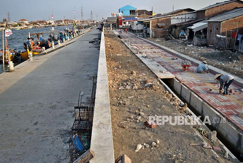 Pekerja membangun trotoar di lokasi pembangunan Kampung Bahari Tambaklorok, Tanjung Emas, Semarang, Jawa Tengah, Jumat (6/4).