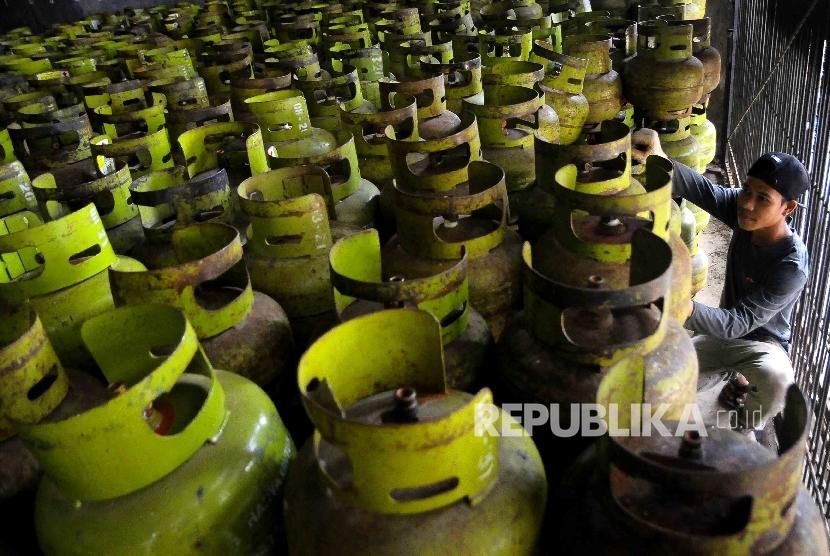 Pekerja membawa tabung gas elpiji tiga kilogram (gas melon).
