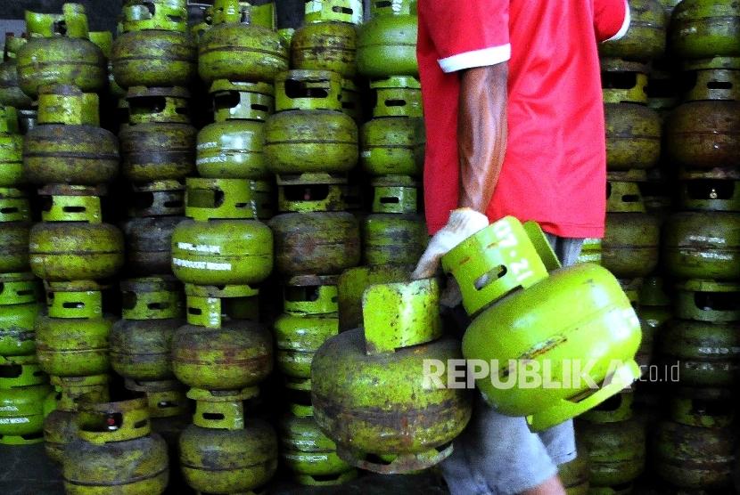 Pekerja membawa tabung gas Elpiji tiga kilogram.