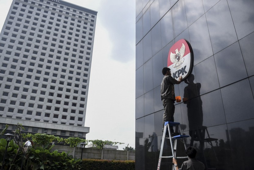 Pekerja membersihkan logo KPK, di Gedung Merah Putih, Jakarta, Senin (5/8).