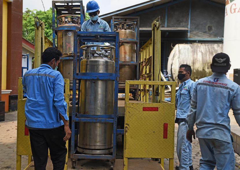 Pekerja membongkar muat tabung gas oksigen di instalasi gas.