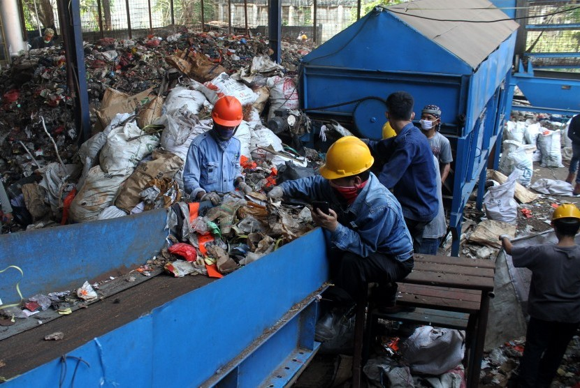 Pekerja memilah sampah saat uji coba pengoperasian mesin instalasi Pembangkit Listrik Tenaga Sampah (PLTSa). ilustrasi