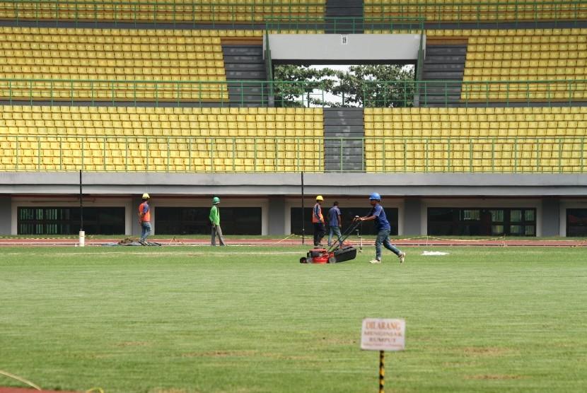 Pekerja memotong rumput lapangan Stadion Patriot Candrabhaga, di Bekasi, Jawa Barat, Kamis (19/7).