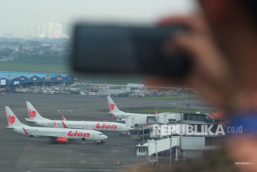 Pekerja memotret sejumlah pesawat Boeing seri 737-800 dan 737-900ER milik Lion Air yang terparkir di Terminal 1 A Bandara Soekarno Hatta, Tangerang, Banten, Jumat (15/3/2019).