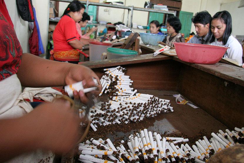 Pekerja memproduksi rokok kretek.