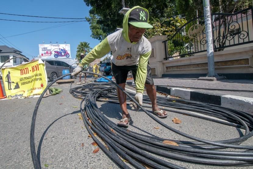 Pekerja menarik kabel serat optik milik PT. Telkom pada proyek pemeliharaan jaringan di Palu, Sulawesi Tengah, Rabu (20/3/2019).