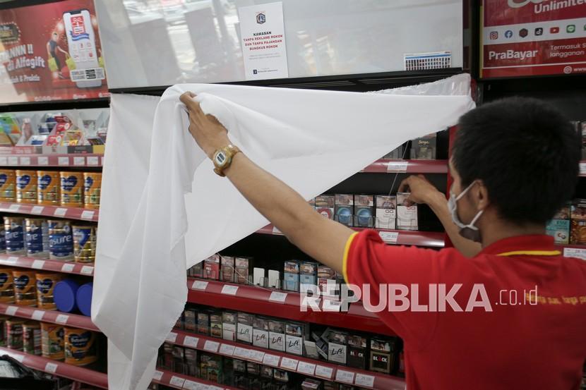 Pekerja menata rokok yang etalasenya ditutup kain di salah satu minimarket di kawasan Jakarta Pusat, Rabu (15/9/2021). Penutupan etalase rokok tersebut dilakukan berdasarkan Seruan Gubernur DKI Jakarta nomor 8 tahun 2021 tentang Pembinaan Kawasan Dilarang Merokok sebagai upaya melindungi masyarakat dari bahaya rokok.