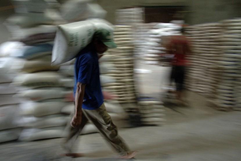 Pekerja mengangkat karung beras di penggilingan beras Jong Biru, Kediri, Jawa Timur, Selasa (29/11).