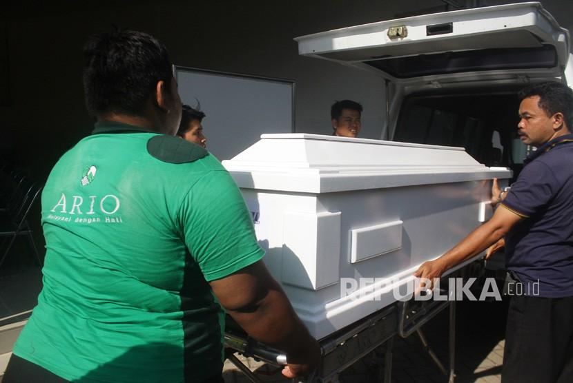 Pekerja mengangkat peti berisi jenazah Mayawati, korban bom gereja Surabaya berada di Rumah Persemayaman Gotong Royong, Malang, Jawa Timur, Senin (14/5).