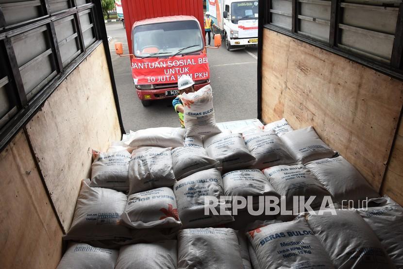 Pekerja mengangkut beras yang akan disalurkan ke dalam truk saat program bantuan sosial beras.