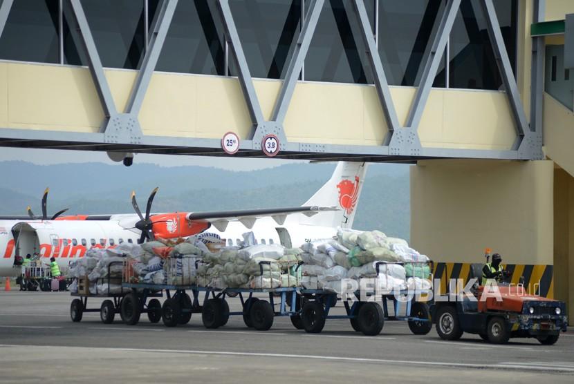 Pekerja mengangkut kargo muatan udara dengan kereta barang di Bandara Internasional Sultan Iskandar Muda (SIM) Blangbintang, Kabupaten Aceh Besar, Aceh, Kamis (17/1/2019).
