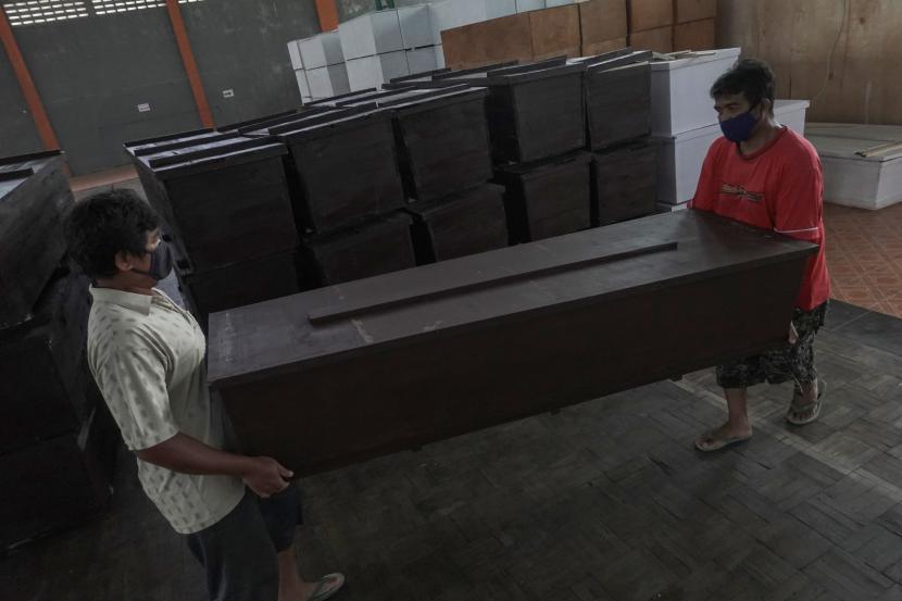 Pekerja mengangkut peti mati yang akan digunakan bagi jenazah pasien COVID-19, di GOR Satria Purwokerto, Banyumas, Jawa Tengah, Senin (26/7/2021). Pemkab Banyumas menerima bantuan peti mati dari sejumlah organisasi masyarakat dan pengusaha, terkait jumlah kematian akibat Covid-19 di Kabupaten Banyumas yang mencapai 602 kasus dari tanggal 1-25 Juli 2021