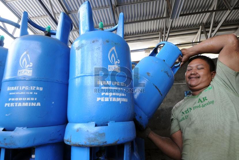 Pekerja mengangkut tabung 12 kilogram berisi liquefied petroleum gas (LPG atau elpiji).