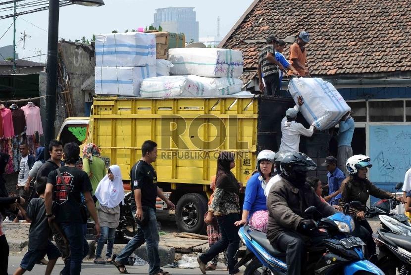 Pekerja mengatur paket di atas truk yang yang mengantarkan barang kiriman dari Pasar Tanah Abang, Jakarta Pusat. Truk tersebut kerap jadi sasaran pungli preman yang meminta sejumlah uang.