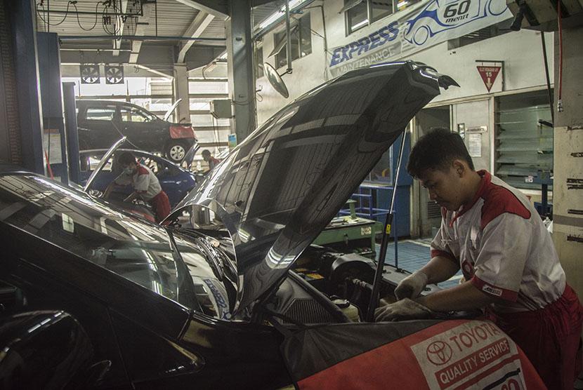 Pekerja mengecek kondisi mobil pelanggan di bengkel mobil Kawasan Tebet, Jakarta, Jumat (8/6).
