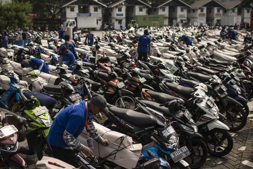 Pekerja mengepak sepeda motor milik pemudik peserta program Angkutan Motor Gratis 2018 di Stasiun Jakarta Gudang, Kampung Bandan, Jakarta, Jumat (8/6).