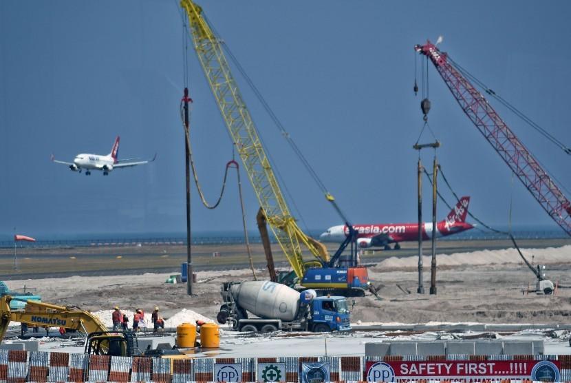 Pekerja menggarap pembangunan apron timur Bandara Internasional I Gusti Ngurah Rai, Kuta, Bali, Jumat (20/7).
