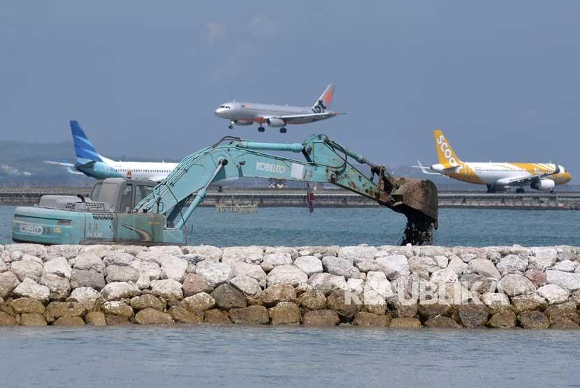 Pekerja menggunakan alat berat melakukan pengerjaan persiapan perluasan apron sisi barat Bandara Internasional Ngurah Rai, Bali, Kamis (3/5).