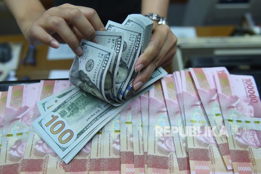 Pekerja menghitung uang Dollar Amerika Serikat dan Rupiah di sebuah tempat penukaran uang di Jakarta, Kamis (28/3/2019).