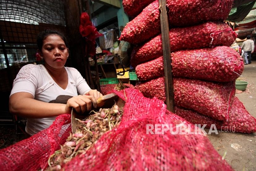 Pekerja mengupas bawang merah di Pasar Induk Kramat Jati, Jakarta, Senin (8/5).