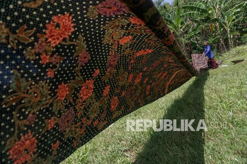Pekerja menjemur kain batik sepanjang sekitar 125-250 meter di Medono, Pekalongan, Jawa Tengah (22/9/2021). Menurut salah satu pekerja, proses penjemuran kain batik memanfaatkan lahan kosong sekitar tempat produksi seperti lapangan bola dengan penjemuran membutuhkan waktu sekitar dua jam kondisi cuaca cerah.