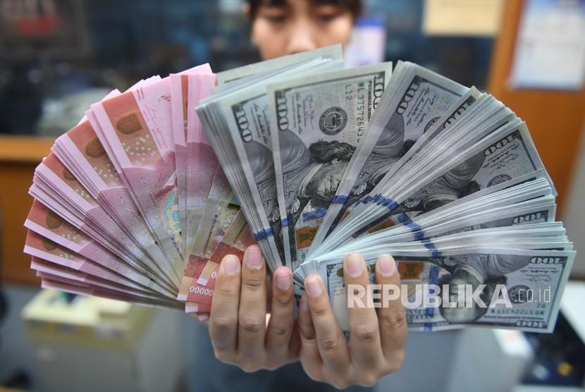 Pekerja menunjukkan uang Rupiah dan Dollar Amerika Serikat di sebuah tempat penukaran uang di Jakarta, Kamis (28/3/2019).