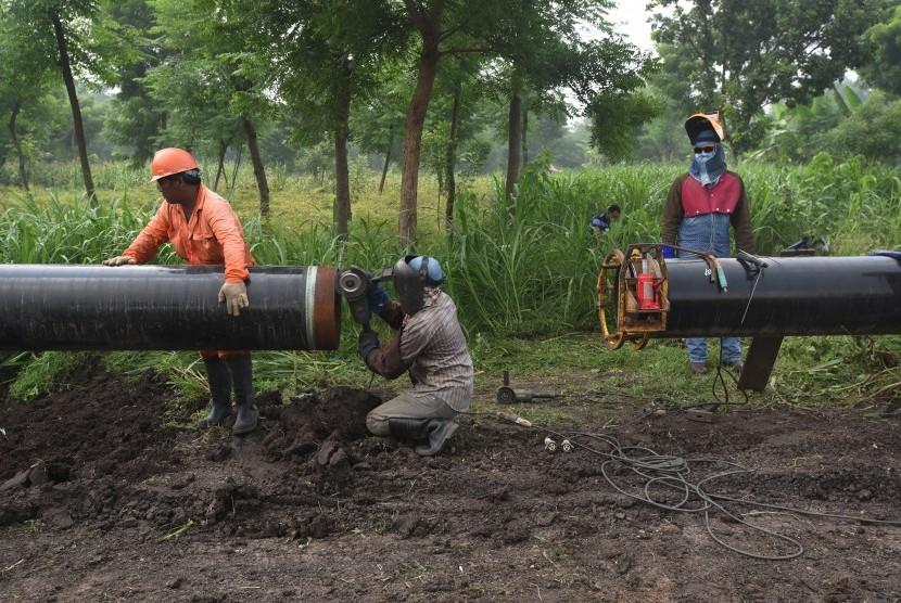 Pekerja menyambung pipa penyaluran gas pada proyek pembangunan pipa transmisi gas ruas Porong - Grati milik Pertamina Gas (Pertagas) di Pasuruan, Jawa Timur.