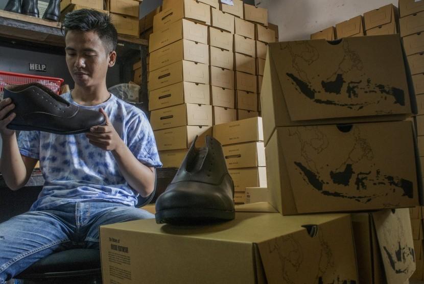 Pekerja menyelasaikan pembuatan sepatu kulit di Industri Rumahan, Bandung, Jawa Barat, Rabu (25/7). I