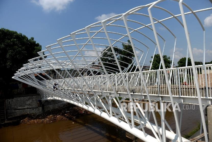 Pekerja menyelesaikan pembangunan jembatan penyeberangan orang (JPO) di Sungai Ciliwung, Manggarai, Jakarta, Rabu (6/4).  (Republika/ Wihdan)