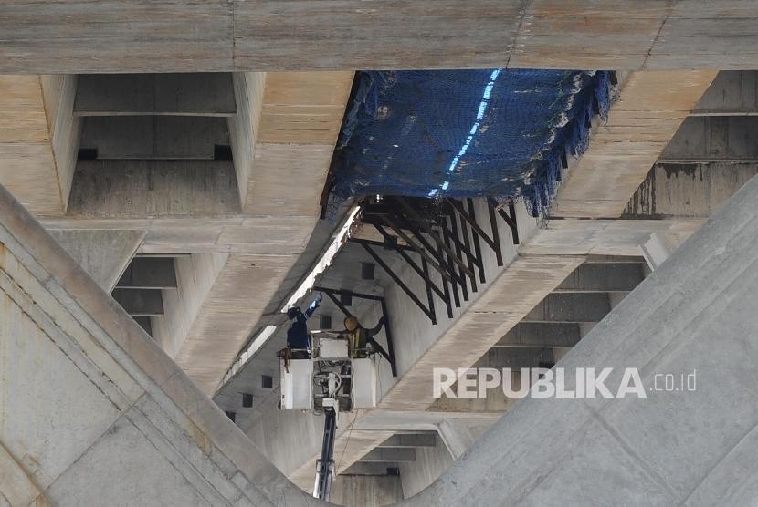 Pekerja menyelesaikan pembangunan tol JORR Tanjung Priok-Cilincing, Jakarta, Ahad (9/10).