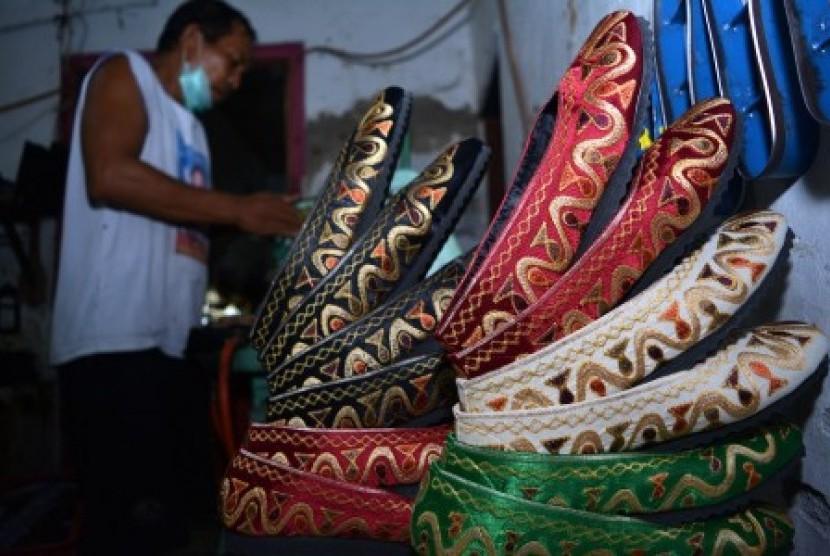 Pekerja menyelesaikan pembuatan sepatu bordir di industri rumahan kawasan Kampung batik Jetis, Sidoarjo, Jawa Timur, Rabu (23/12).