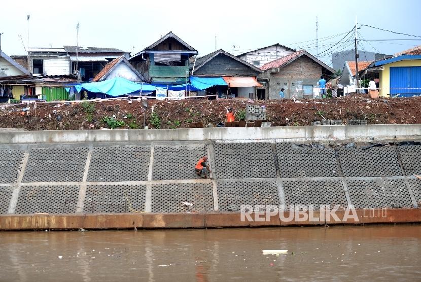 Pekerja menyelesaikan proyek normalisasi Sungai Ciliwung di Bukit Duri, Jakarta, Jumat (10/2).