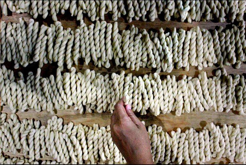 Pekerja menyusun kue Tali-Tali yang siap digoreng di rumah produksi, Kamis, (24/5).
