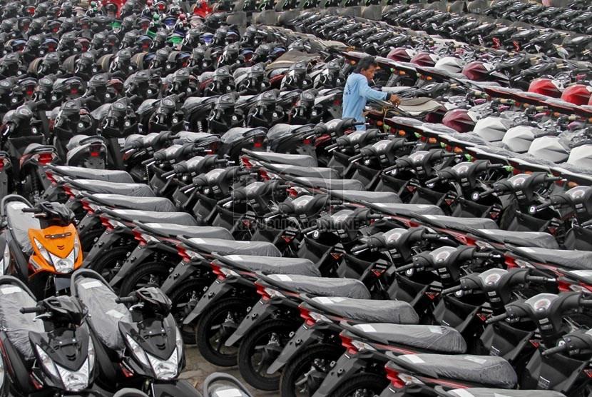 Pekerja merapihkan sepeda motor yang siap dikirim ke sejumlah daerah di pelabuhan Tanjung Priok, Jakarta, Kamis (21/3).
