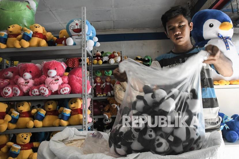 Pekerja merapikan boneka yang akan dikirim di kokao toys mart, Bekasi, Jawa Barat, Sabtu (18/9/2021). OJK memperluas akses keuangan melalui pembentukan skema KUR Klaster.