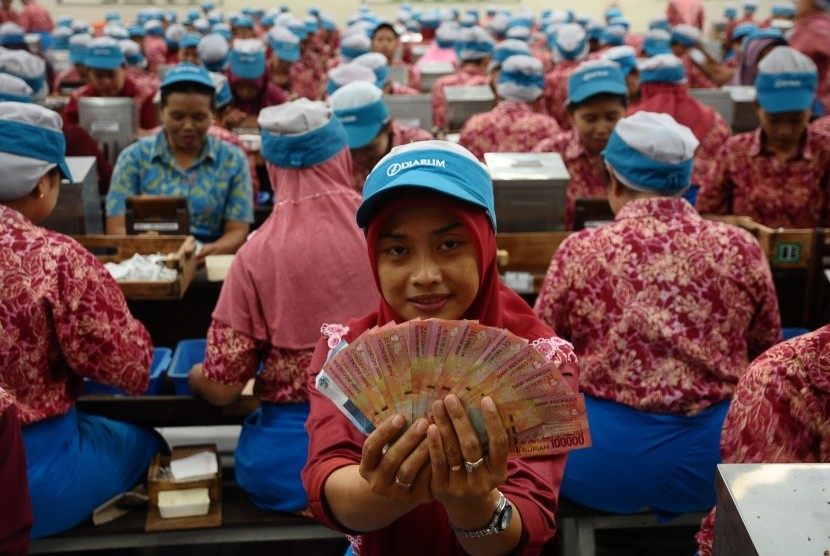 Pekerja pabrik menunjukkan uang  Tunjangan Hari Raya (THR) Lebaran di Kudus, Jawa Tengah, Kamis (15/6).