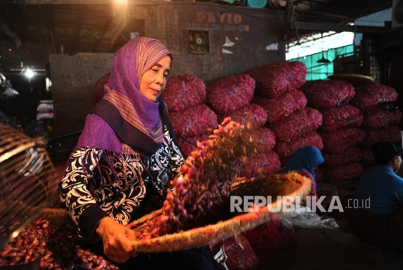 Pekerja sedang membersihkan bawang merah di pasar Induk, Jakarta, Selasa (19/4). (Republika/Tahta Aidilla )